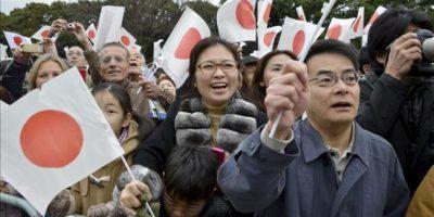Simpatizantes japoneses ondean banderas nacionales, mientras celebran el 79 cumpleaños del emperador Akihito, hoy a las puertas del Palacio Imperial en Tokio. EFE