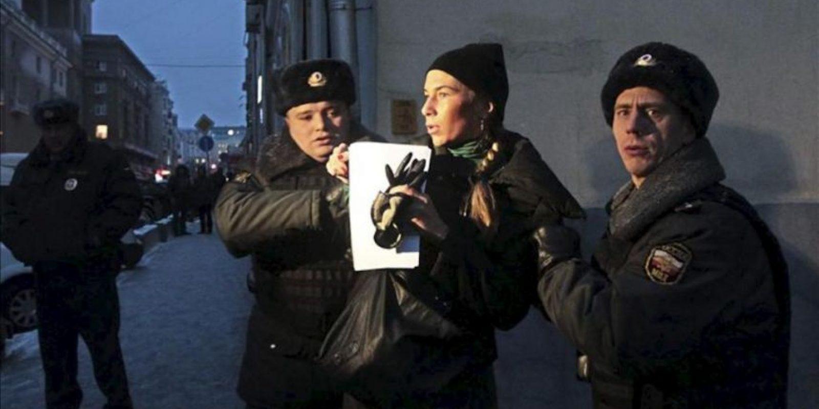 La policía detiene a una mujer que protesta contra de la prohibición de adopción de huérfanos rusos a ciudadanos americanos a las puertas del Consejo de la Federación en Moscú. EFE
