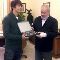 El jugador del Atlético de Madrid Oliver Torres (i) recibe de manos del alcalde de Navalmoral de la Mata, Rafael Mateos, una placa conmemorativa durante el homenaje que el futbolista ha recibido hoy en el Ayuntamiento de su ciudad natal. EFE