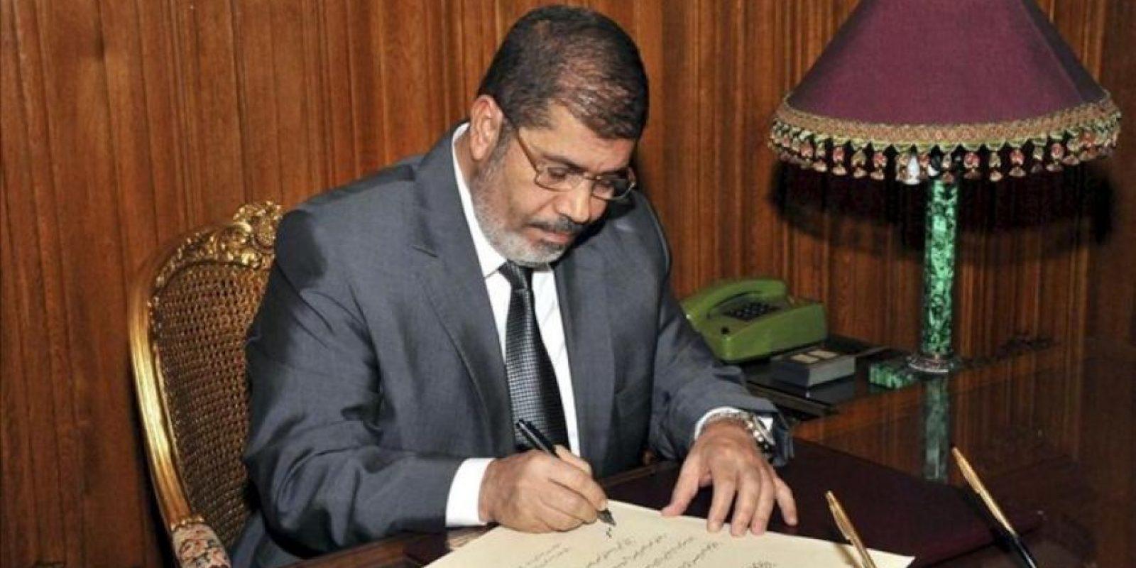 """Imagen cedida por la presidencia de Egipto el 26 de diciembre del 2012 muestra al presidente Mohamed Mursi firmando un decreto para aprobar la nueva Constitución, en El Cairo, Egipto, el 25 de diciembre del 2012, tras un referéndum popular con el 63,8% de los votos al """"sí"""". EFE/Presidencia de Egipto"""