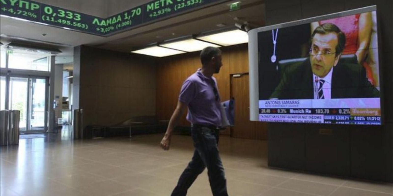 Un hombre pasa delante de una pantalla que muestra a Antonis Samaras, líder del partido Nueva Democracia, en la Bolsa de Atenas (Grecia). EFE/Archivo