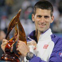 El tenista serbio Novak Djokovic levanta el trofeo que le acredita como vencedor del torneo de exhibición de Abu Dabi tras vencer al español Nicolás Almagro, hoy. EFE