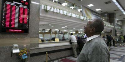 Un hombre revisa un panel con el valor alcanzado por varias divisas en un banco de El Cairo (Egipto) hoy, lunes 31 de diciembre de 2012. EFE