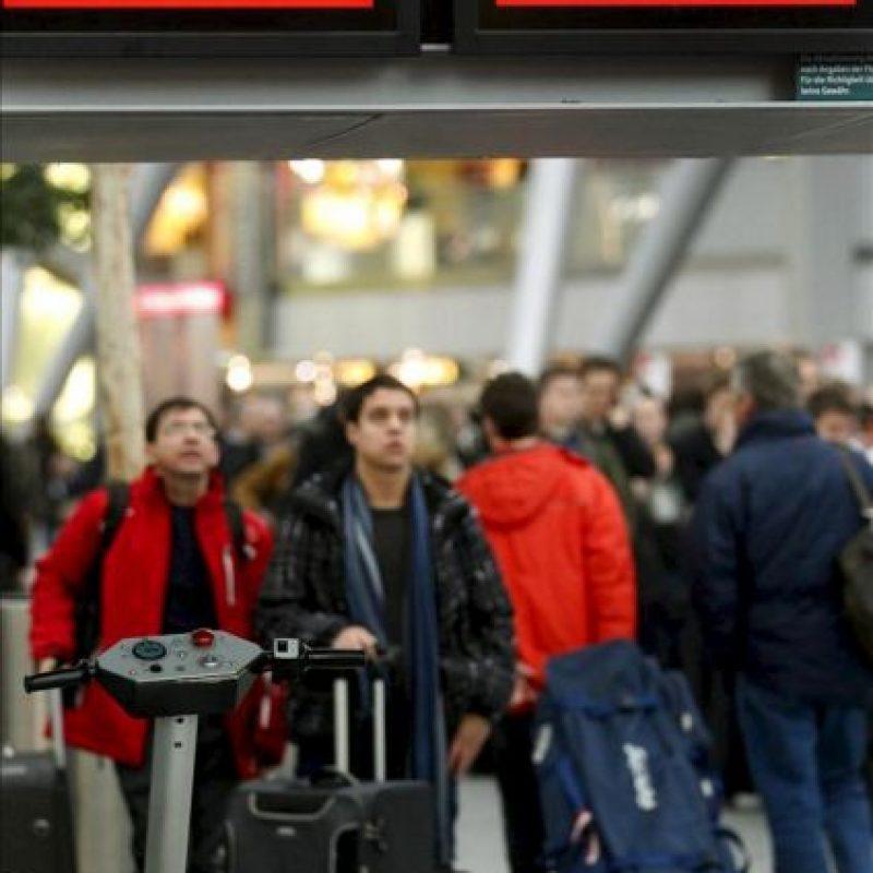 Varios pasajeros observan las pantallas de información antes de dirigirse a los mostradores de facturación en el aeropuerto de Düsseldorf (Alemania). EFE