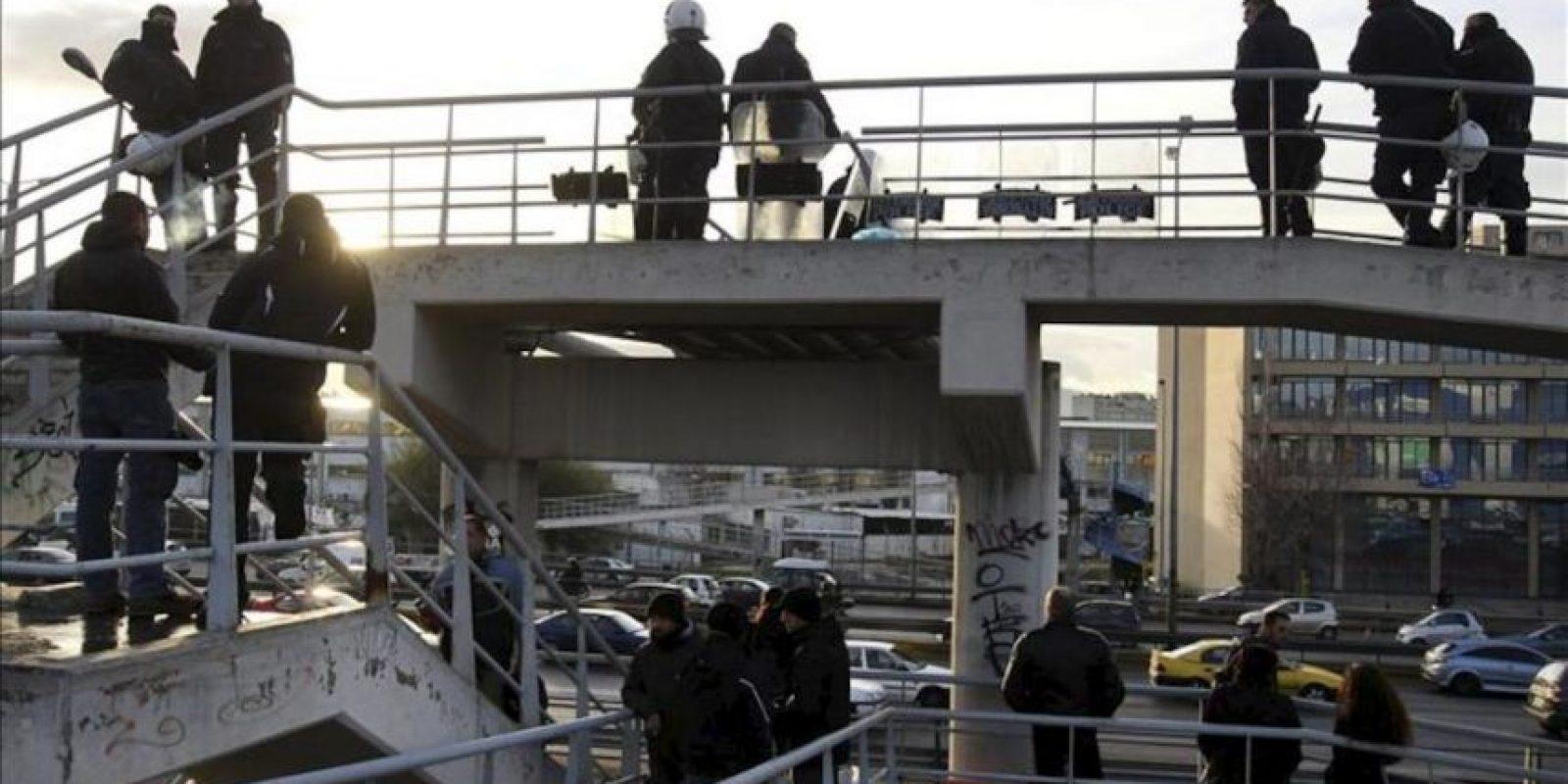 Varios policías antidisturbios desplegados en un paso elevado que conduce a la cocheras del metro de Atenas hoy en Atenas (Grecia). EFE