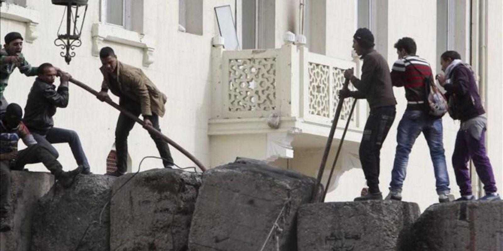 Unos hombres intentan derribar el muro recientemente erigido para proteger la entrada al Parlamento en las proximidades de la plaza Tahrir de El Cairo, Egipto. EFE