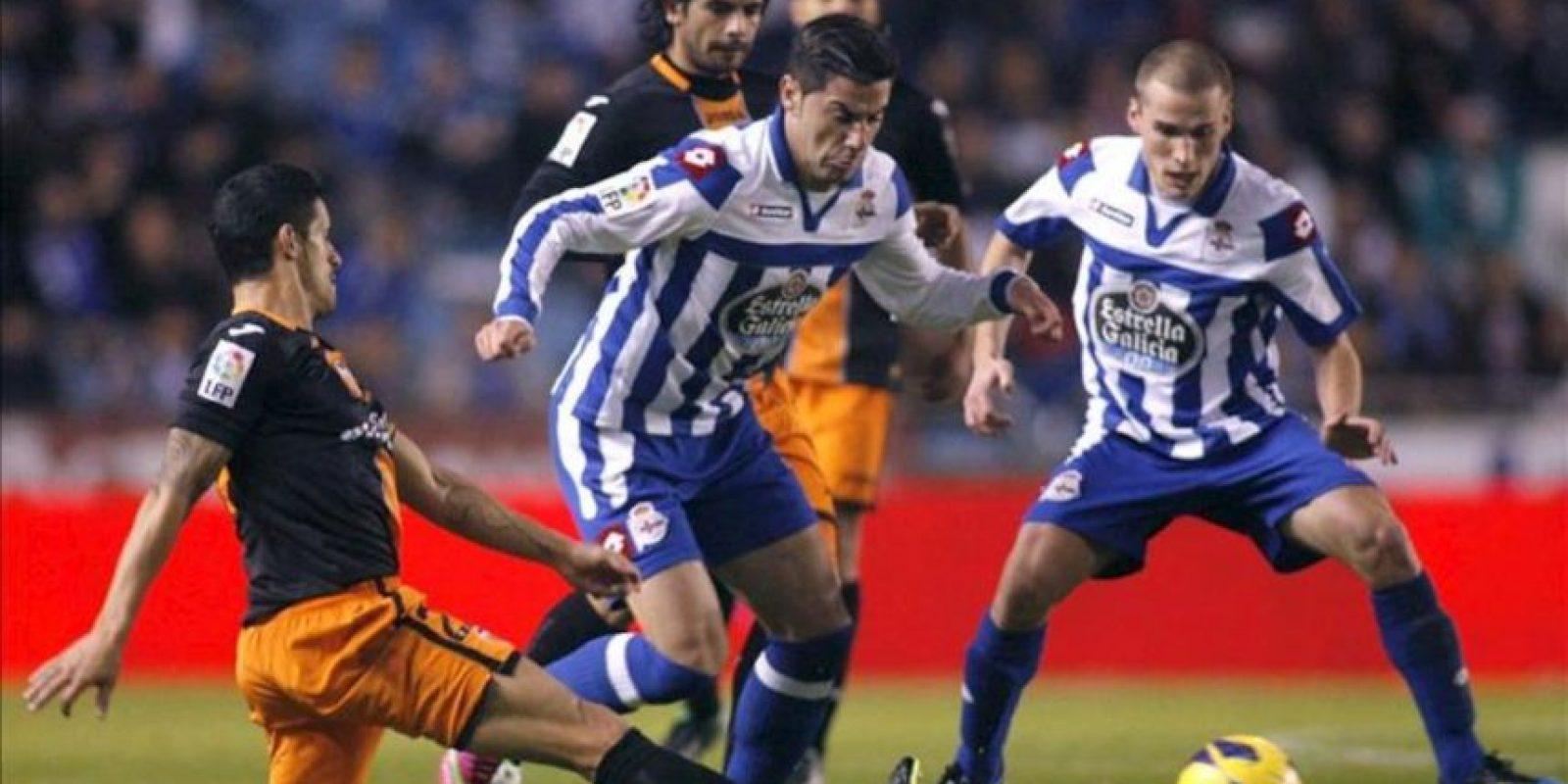 El delantero del Deportivo de La Coruña, Riki (c), intenta superar la entrada del defensa portugués del Valencia, Ricardo Costa (i), durante el encuentro correspondiente a la jornada 21 de primera división, que han disputado en el estadio de Riazor, en A Coruña. EFE