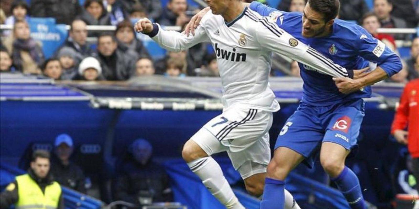 El delantero portugués del Real Madrid, Cristiano Ronaldo (i), intenta controlar el balón ante el defensa del Getafe, Rafa López (d), durante el partido correspondiente a la vigésimo primera jornada de la Liga de fútbol de Primera División en el estadio Santiago Bernabéu, en Madrid. EFE