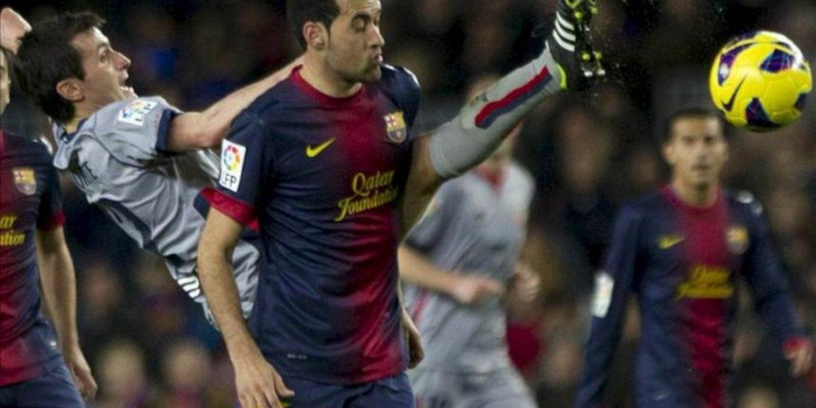 El delantero del Osasuna Joseba Llorente (izq) intenta alcanzar el balón ante la oposición del centrocampista del FC Barcelona Sergio Busquets, durante el partido de la vigésimo primera jornada de Liga de Primera División disputado en el Camp Nou de Barcelona. EFE