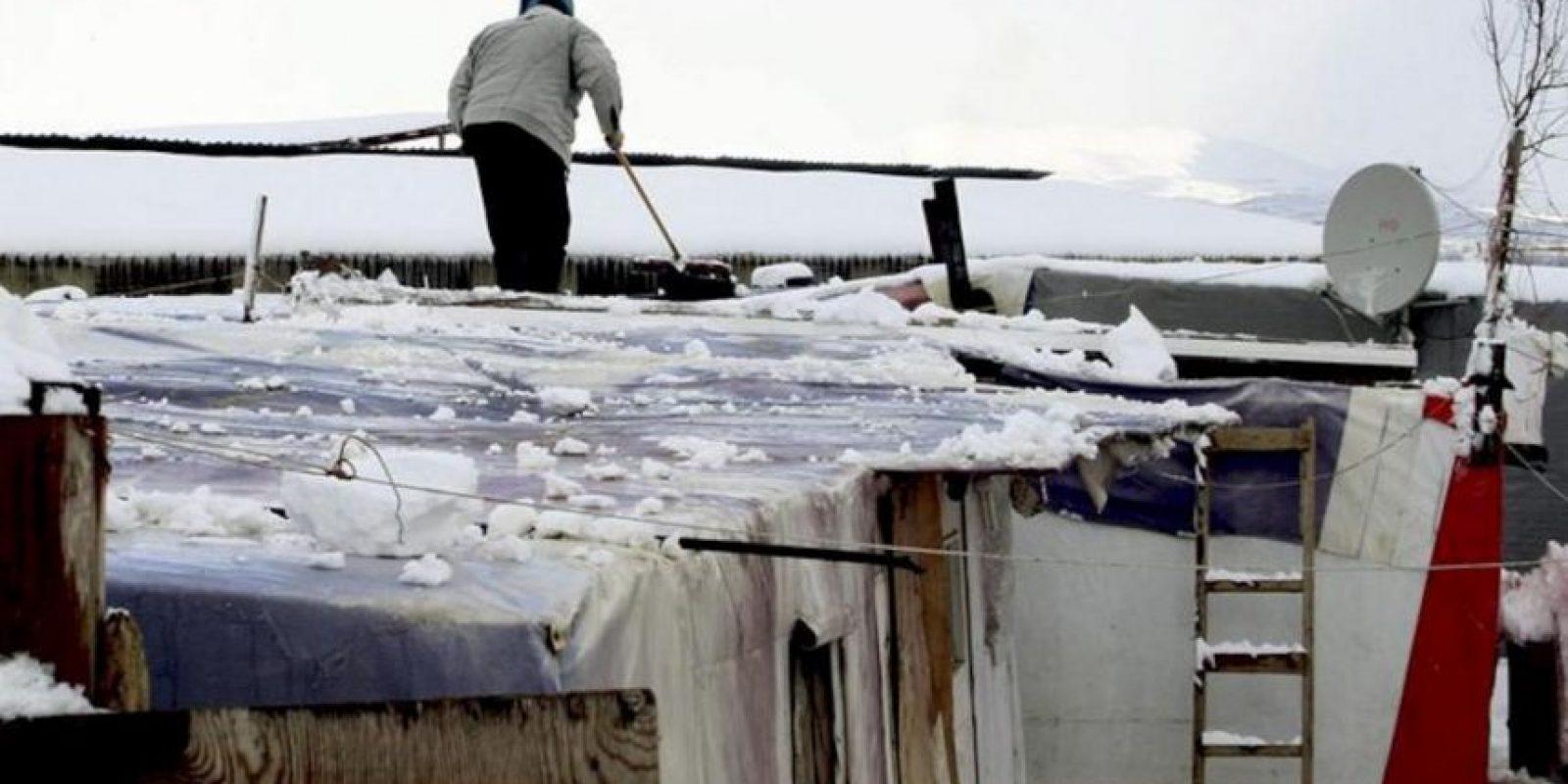 Un refugiado sirio limpia la nieve del techo de su tienda de campaña en la villa de Deirzanoun, en el valle de Bekaa, en el este del Líbano. EFE/Archivo