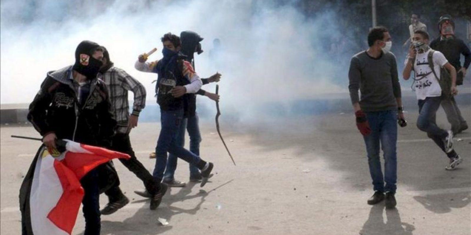 Jóvenes egipcios huyen este domingo de los gases lacrimógenos durante los enfrentamientos con las fuerzas de seguridad egipcias cerca de la Plaza Tahrir en El Cairo (Egipto). EFE