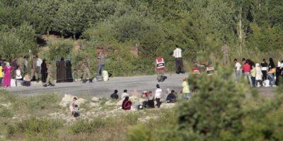 Refugiados sirios esperan en la localidad de Guvecci, en la frontera entre Siria y Turquía a ser trasladados a un campamento de la Media Luna Roja en Turquía. EFE/Archivo
