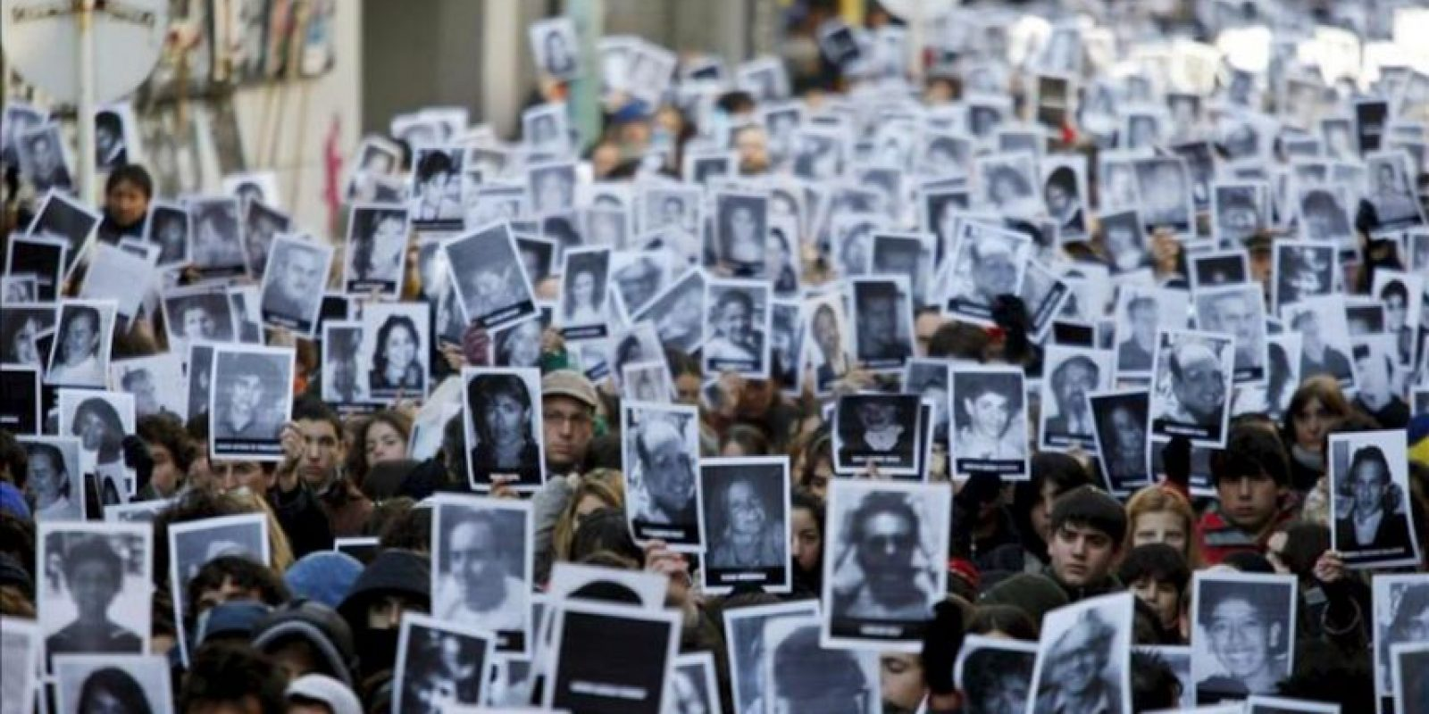 Cientos de personas llevando fotografías de las víctimas asisten el 16 de julio de 2010, al acto por el 16 aniversario del atentado a la mutual judía AMIA que causó la muerte de 85 personas en Buenos Aires (Argentina). EFE/Archivo