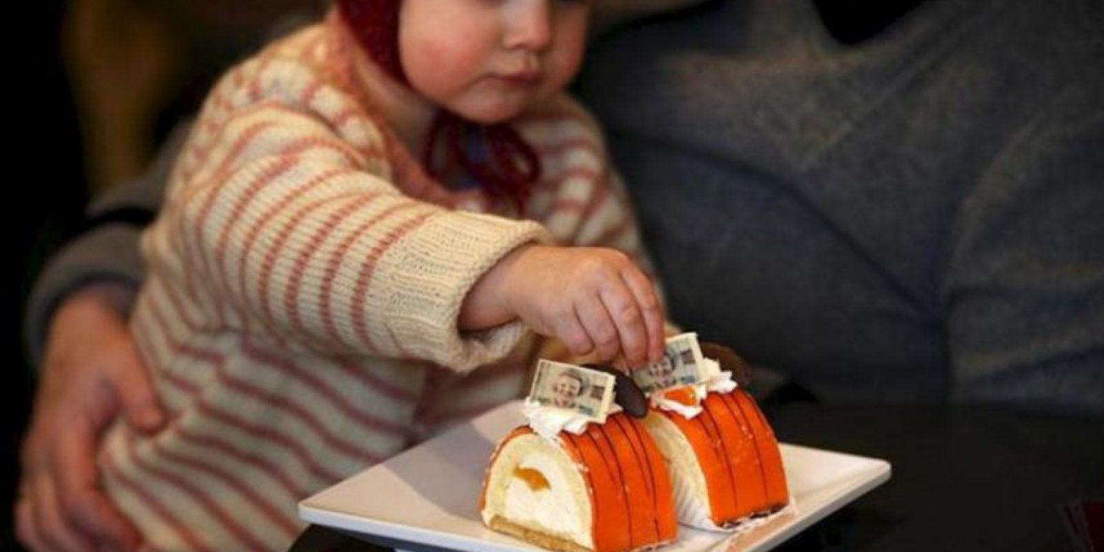 Una niña come un pastel de naranja con la fotografía de la reina Beatriz de Holanda, en una pastelería de Leeuwarden, Holanda, el 29 de enero de 2013. EFE