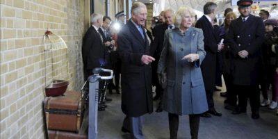 El príncipe de Gales Carlos de Inglaterra (c-izq), y su esposa Camila (c-dcha), duquesa de Cornualles, posan en el andén 9 y 3/4 de la estación de King Cross en Londres (Reino Unido) mientras visitan la estación para celebrar el 150º aniversario del Metro de Londres, hoy, miércoles 30 de enero de 2013. Esta red del transporte público londinense celebra este año sus 150 años de existencia. EFE