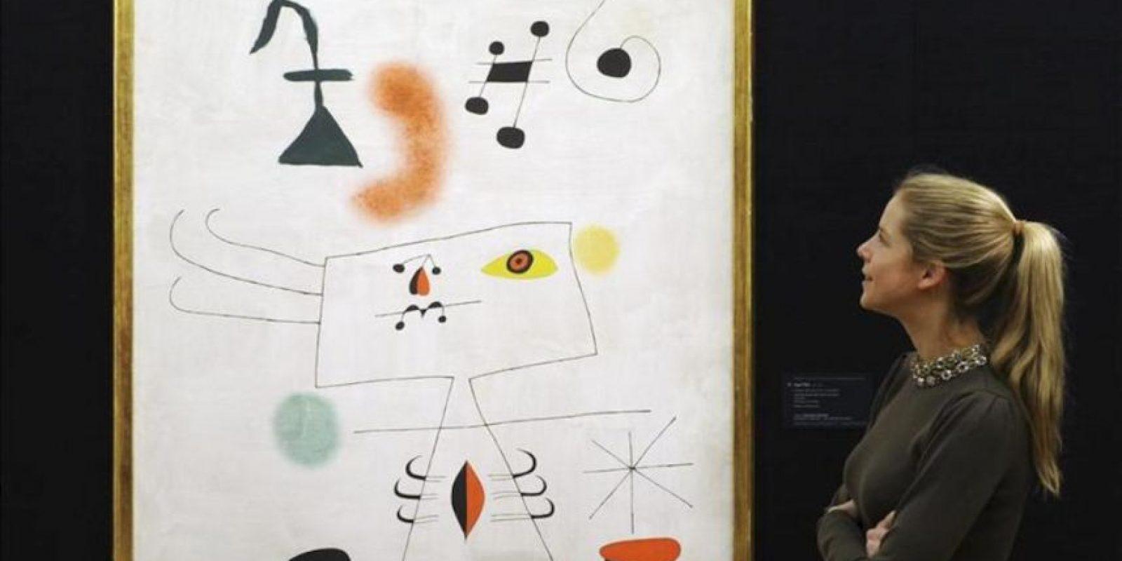 """Una empleada de Sotheby's observa el cuadro """"Femme revant de l'evasion (Mujer soñando con escapar)"""" (1945), del artista español Joan Miró, en la casa de subastas de arte contemporáneo de Sotheby's en Londres (Reino Unido). Esta obra, que saldrá a subasta el próximo 12 de febrero, se espera que alcance un precio de venta de entre 10 y 14 millones de euros. EFE/Andy Rain"""