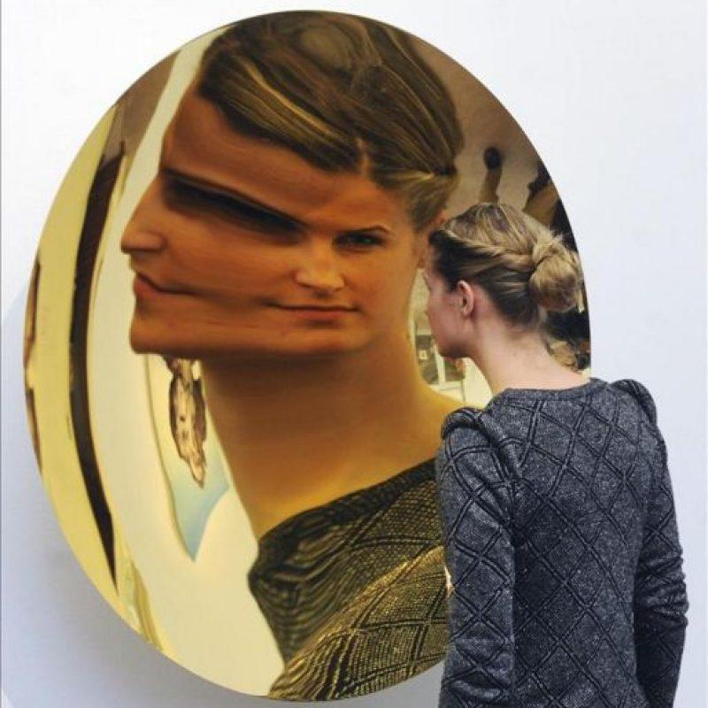 Una empleada de Sotheby's se refleja en un espejo dorado sin título del artista británico de origen indio Anish Kapoor en la casa de subastas de arte contemporáneo de Sotheby's en Londres, Reino Unido. Esta obra, que saldrá a subasta el próximo 12 de febrero. EFE