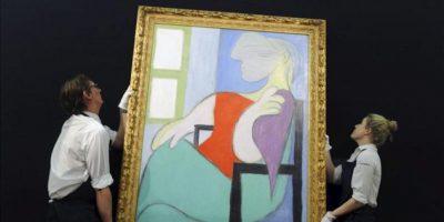 """Unos empleados de Sotheby's cuelgan el cuadro """"Mujer sentada frente a una ventana"""" (1932), del artista español Pablo Ruiz Picasso, en la casa de subastas de arte contemporáneo de Sotheby's en Londres (Reino Unido). Esta obra, que saldrá a subasta el próximo 12 de febrero. EFE"""