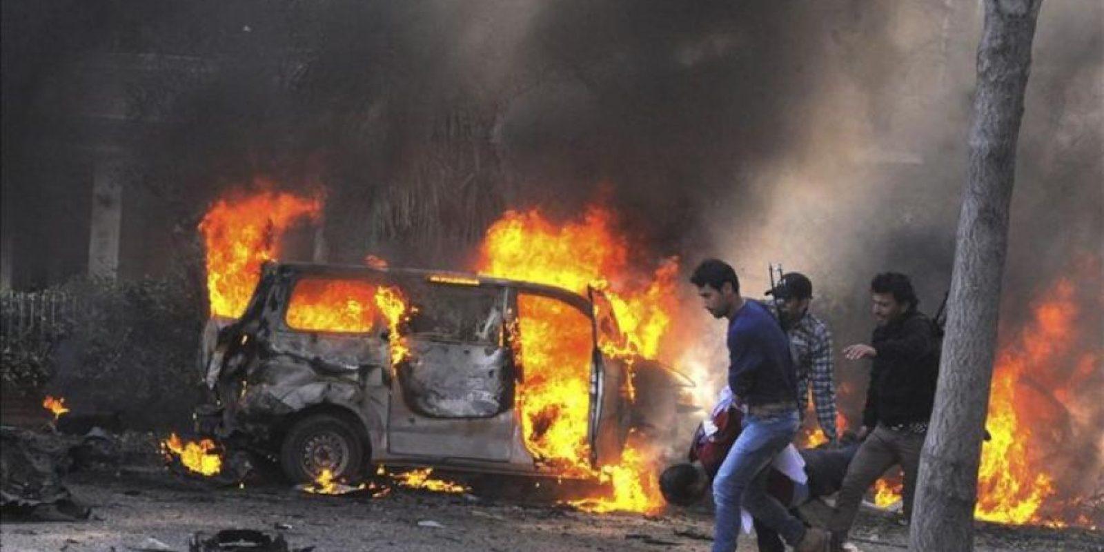Fotografía distribuida por la agencia de noticias oficial siria SANA que muestra a tres rebeldes sirios que llevan en volandas a un hombre que resultó herido tras la gran explosión causada hoy por un coche bomba en el centro de Damasco. EFE/SANA
