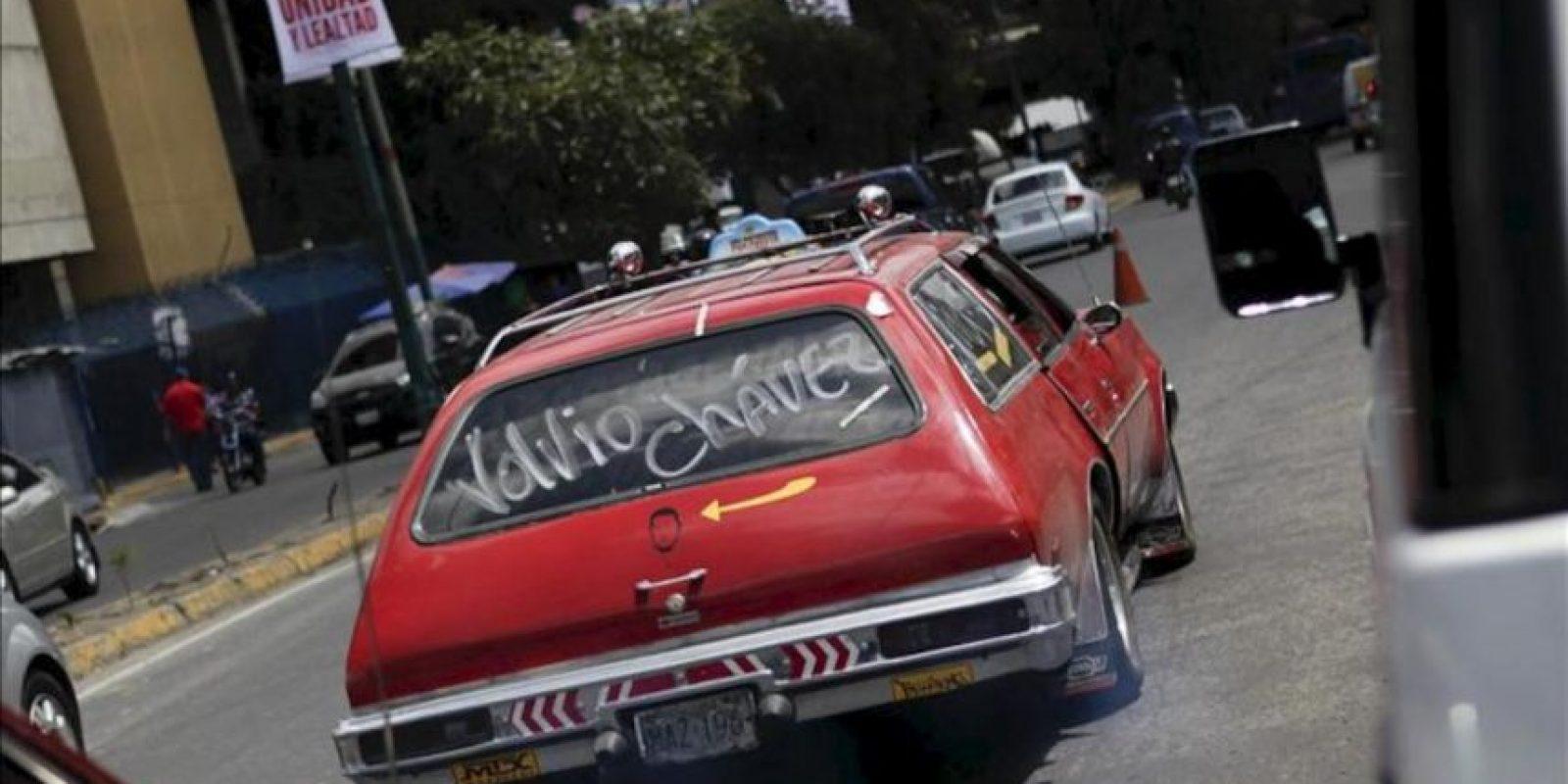 """Un vehículo con un mensaje de apoyo al presidente venezolano Hugo Chávez cruza frente al Hospital Militar """"Dr. Carlos Arvelo"""", en Caracas (Venezuela). EFE"""