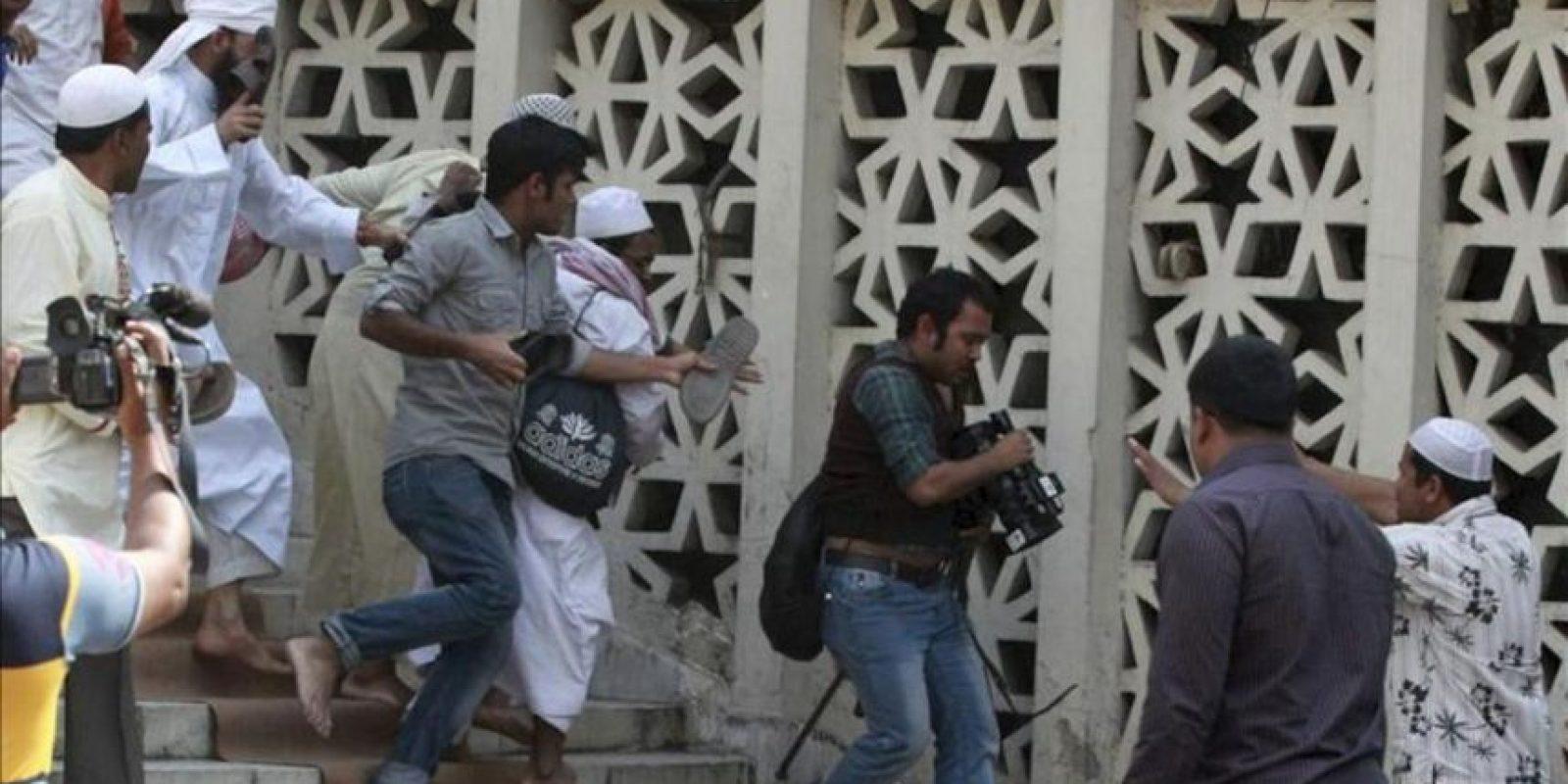 Activistas islámicos agreden a periodistas durante unos disturbios con la policía en los arededores de la mezquita nacional de Baitul Mukarram en Dacca (Bangladesh) hoy, viernes 22 de febrero de 2013. EFE