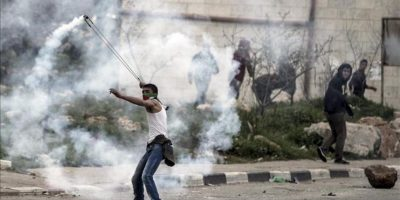 Un joven palestino lanza con una honda un bote de gases lacrimógenos que a su vez fue lanzada por policías de frontera israelíes durante los disturbios registrados hoy cerca de la prisión militar de Ofer en Betunia, al sur de Ramala, Cisjordania. EFE