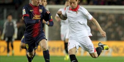 El centrocampista croata del Sevilla Ivan Rakitic (d) con el balón ante el delantero argentino del F.C. Barcelona Lionel Messi (i), durante el partido de la vigésimo quinta jornada de Liga de Primera División disputado en el Camp Nou de Barcelona. EFE