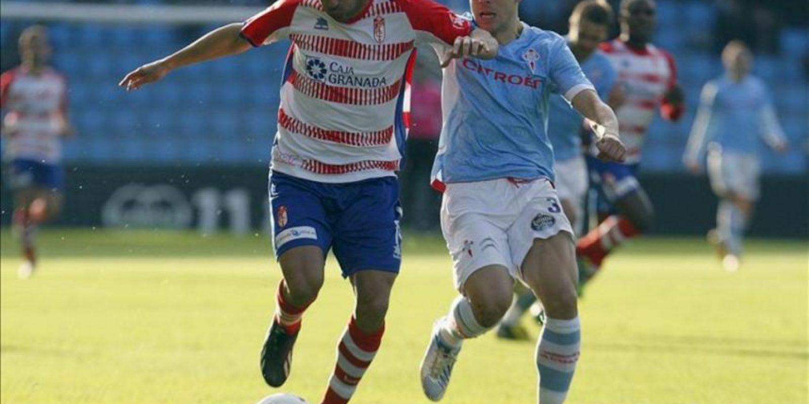 El delantero del Granada Carlos Reina Aranda y el defensa del Celta de Vigo Roberto Lago (d) luchan por el balón, durante el partido de la vigésimo quinta jornada de Liga de Primera División disputado en el estadio de Balaidos. EFE