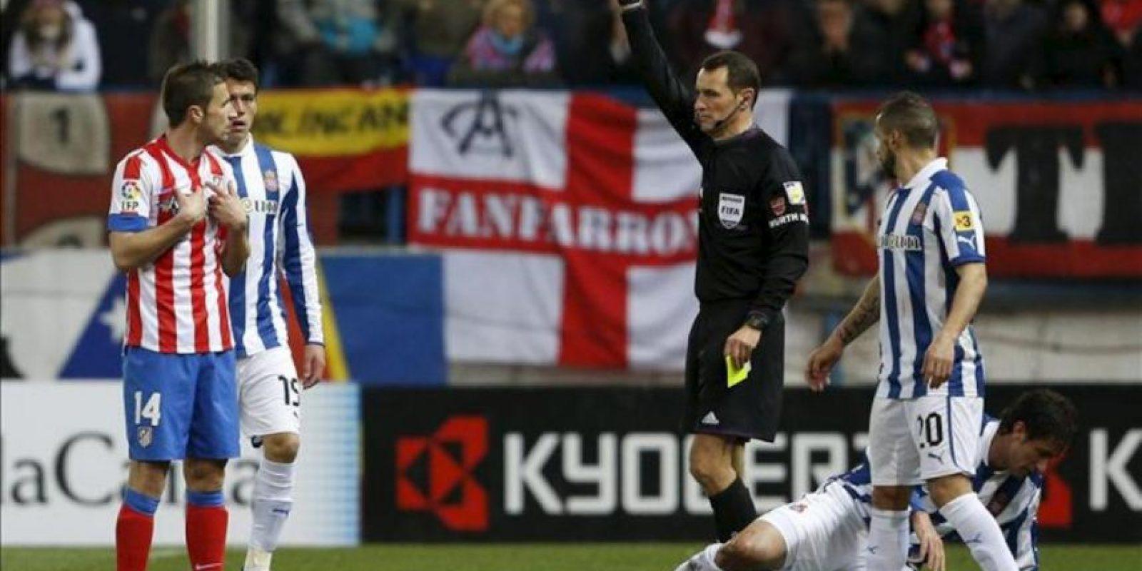 El árbitro del encuentro, Carlos Clos Gómez, saca tarjeta roja al centrocampista del Atlético de Madrid Gabi Fernández (i) durante el partido de la vigésimo quinta jornada de Liga de Primera División disputado ante el RCD Espanyol en el estadio Vicente Calderón. EFE