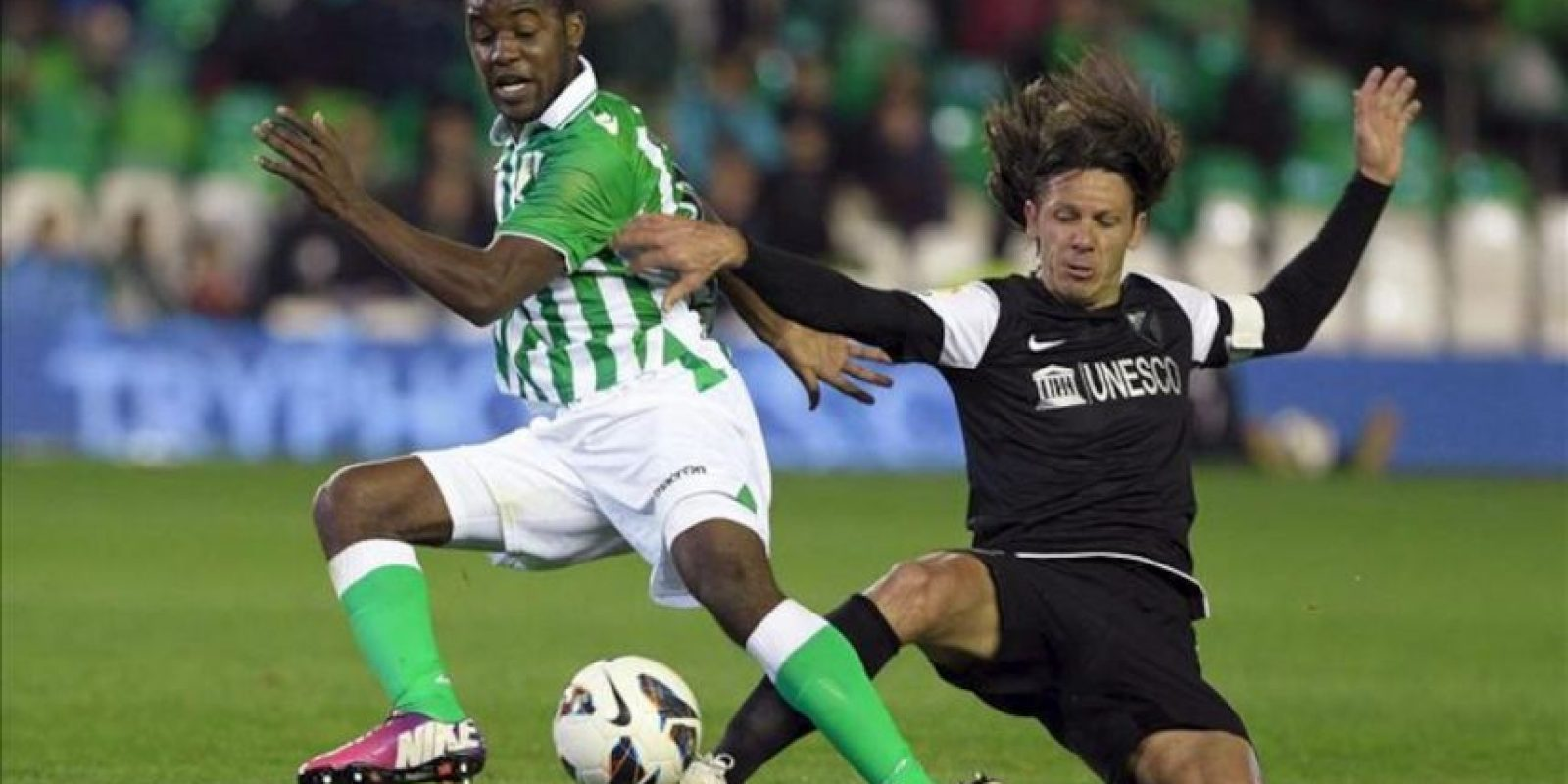 El delantero costarricense del Real Betis Joel Campbell (i) lucha un balón con el defensa argentino del Málaga Martín Demichelis durante el partido de la vigésimo quinta jornada de Liga de Primera División disputado en el estadio Benito Villamarín de Sevilla. EFE