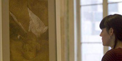 """Una mujer observa hoy el dibujo de grandes dimensiones, titulado """"Personaje con pipa"""", que podría ser obra de Pablo Picasso y que ha aparecido en el reverso del cuadro """"Retrato de la madre del artista"""" (1896), durante su restauración. EFE"""