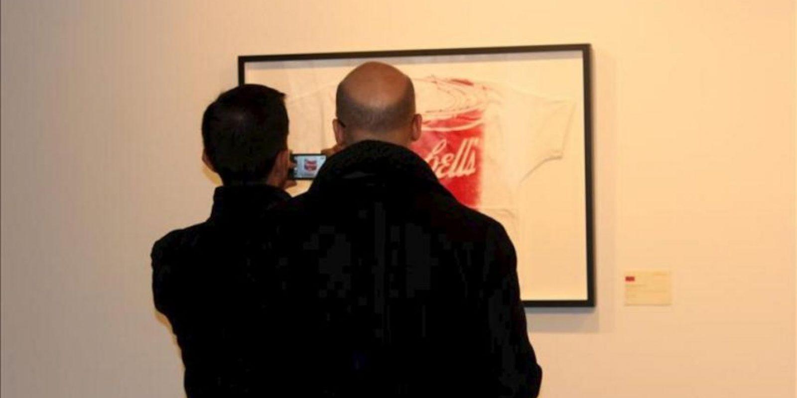 """Un hombre toma una fotografía del """"Campbell's Tomato Soup"""", la camiseta con el dibujo de la lata de sopa Campbell, con un precio estimado de entre 12.000 y 15.000 dólares"""", una de las litografías en colores de Andy Warhol y que sale a la venta en una subasta por internet en la que los amantes del arte podrán pujar durante siete días por sus obras. EFE"""