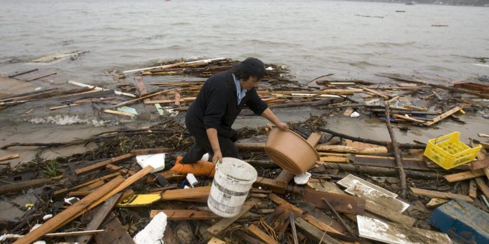 Doris Andrade recolectaba agua del mar el lunes 1 de marzo de 2010, tras el maremoto en la localidad de Dichato, a 475 kilómetros al sur de Santiago (Chile), a raíz del terremoto de 8,8 grados en la escala de Richter que sacudió el sábado 27 de febrero de 2010 el centro y sur de Chile. Foto:Archivo EFE/Ian Salas
