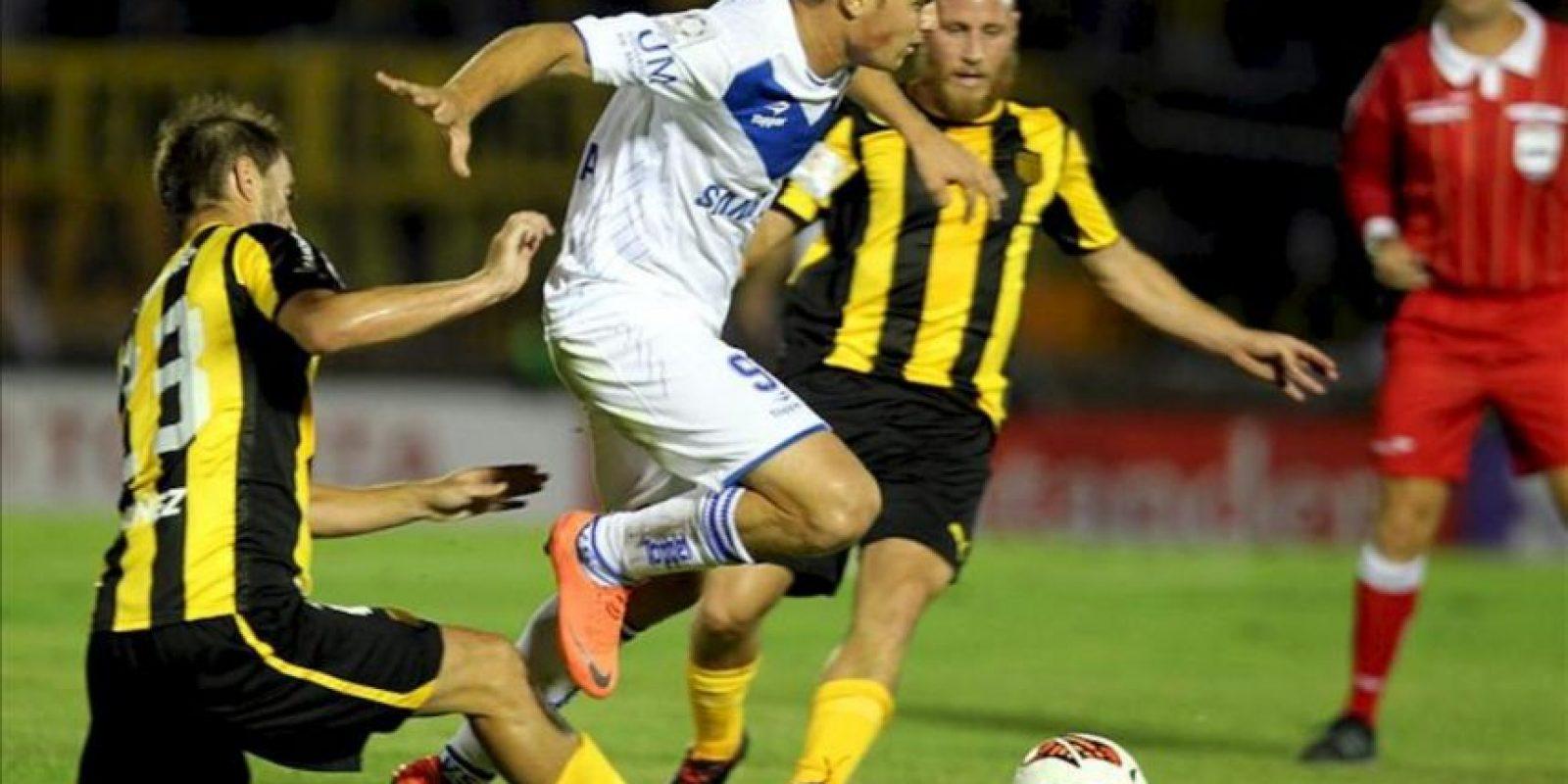 El jugador Ezequiel Rescaldani (c) de Vélez Sarsfield de Argentina disputa el balón con Carlos Valdez (i) de Peñarol de Uruguay durante un partido por la segunda fase de la Copa Libertadores en el estadio Centenario. EFE