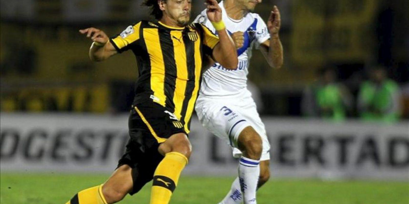 El jugador Emiliano Papa (d) de Vélez Sarsfield de Argentina disputa el balón con Matías Aguirregaray (i) de Peñarol de Uruguay durante un partido por la segunda fase de la Copa Libertadores en el estadio Centenario. EFE