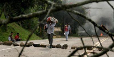 Un grupo de personas cruza una zona bloqueada en la vía Panamericana, en el suroccidente de Colombia. EFE