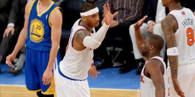 Carmelo Anthony (c) y Raymond Felton (d) de los Knicks celebran ante Stephen Curry (i) de los Warriors durante un juego de la NBA en el Madison Square Garden en Nueva York (EEUU). EFE