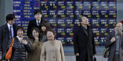 Viandantes caminan hoy frente a una pantalla que muestra los indicadores de las principales bolsas mundiales, en Tokio, Japón. EFE
