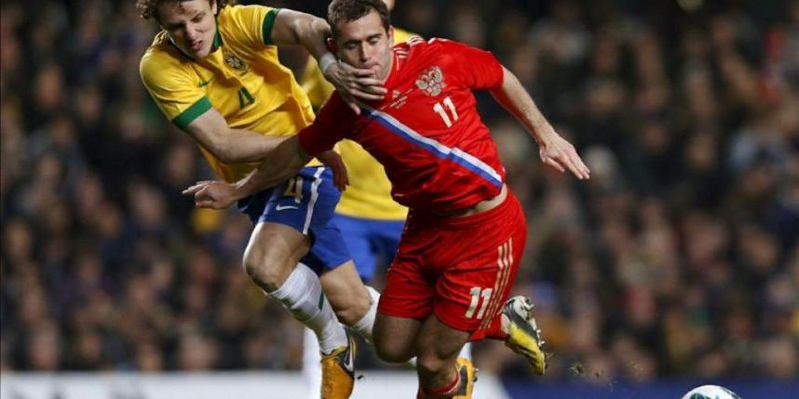 El jugador de Brasil, David Luiz, disputa el balón con Aleksandr Kerzhakov (d) de Rusia, durante el juego amistoso entre las dos selecciones que se disputa en el Stamford Bridge de Londres (R. Unido). EFE