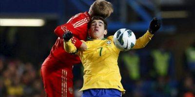 El jugador de Brasil, Oscar disputa el balón con Denis Glushakor (i) de Rusia, durante el juego amistoso entre las dos selecciones que se disputa en el Stamford Bridge de Londres (R. Unido). EFE