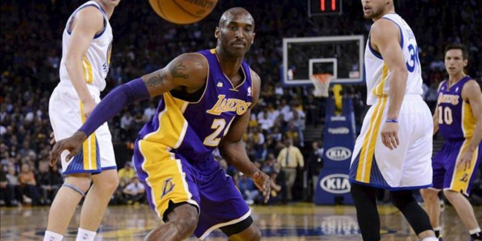 Kobe Bryant (c) de los Lakers de Los Ángeles observa la bola como sale del campo ante Klay Thompson (i) y Stephen Curry (2d) de los Warriors de Golden State, durante su partido de baloncesto de la NBA en Oakland (EE.UU.). EFE