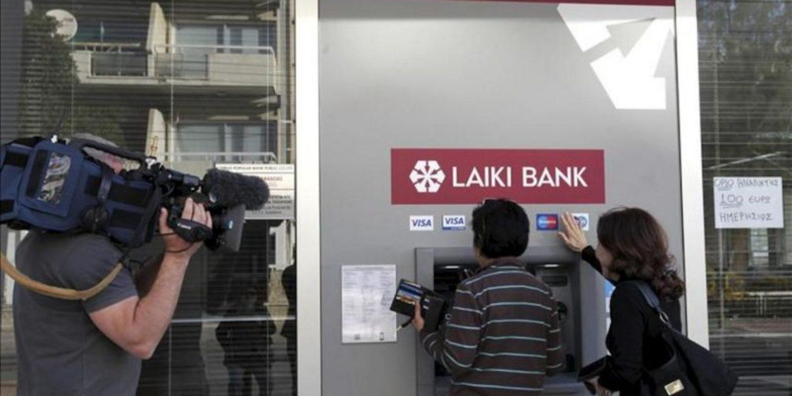 Un cámara graba a dos personas haciendo uso hoy de un cajero automático de una sucursal del banco Laiki, en cuyo escaparate hay un cartel (d) que informa de un límite de 100 euros de retirada de efectivo, en Nicosia, Chipre. EFE