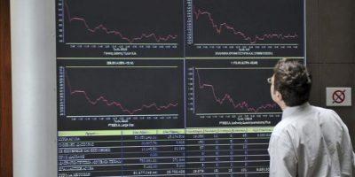 Un hombre observa unos gráficos en el panel de la Bolsa de Atenas en la capital griega hoy. EFE