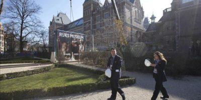 """Un par de trabajadores pasan delante de un cartel del cuadro """"La Ronda de Noche"""", la obra maestra del pintor holandés del claroscuro Rembrandt van Rijn, expuesto a las puertas del Rijksmuseum de Amsterdam (Holanda) hoy. EFE"""