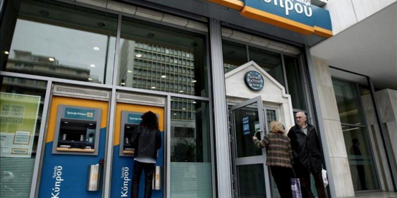 Un hombre retira dinero de un cajero automático de una sucursal del Banco de Chipre en Atenas (Grecia) hoy. EFE