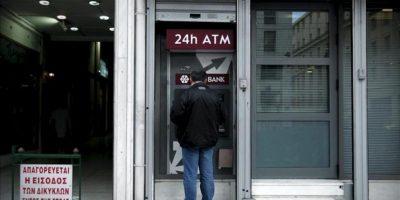 Un hombre saca dinero de un cajero automático en una sucursal del Banco Popular de Chipre en Atenas (Grecia) hoy. EFE