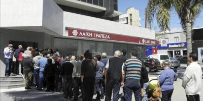 Varias personas hacen cola a las puertas de una sucursal de Laiki Bank en Limassol (Chipre) hoy, jueves 28 de marzo de 2013. Nerviosismo, preocupación y enfado eran los sentimientos que dominaban entre las primeras personas que se acercaron hoy a sus oficinas bancarias de Chipre, en el día de su reapertura. EFE