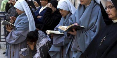 Varias monjas católicas rezan delante de la Iglesia del Santo Sepulcro en el casco viejo de Jerusalén (Israel) a primeras horas de la mañana de hoy mientras esperan la apertura de la iglesia para participar en las celebraciones del Viernes Santo. EFE