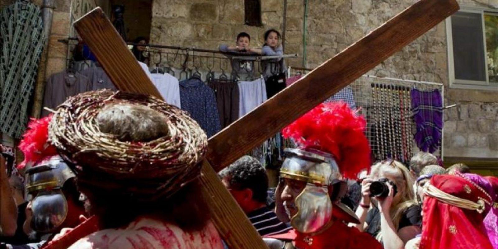 Un par de niños palestinos observan desde un balcón a un grupo religioso estadounidense de Los Ángeles que recrea el trayecto de Jesucristo a la Cruz en la Vía Dolorosa en el casco viejo de Jerusalén (Israel) hoy, viernes 29 de 2013, durante las celebraciones del Viernes Santo. EFE