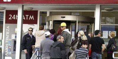 Varias personas hacen cola a las puertas de una sucursal del Banco Laiki en Nicosia (Chipre) hoy, viernes 29 de marzo de 2013. Tras un arranque sin mayores contratiempos el jueves, los bancos chipriotas tienen hoy su segunda jornada de apertura al público y la última de la semana para la mayoría de ellos. EFE